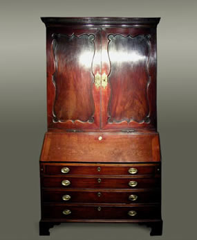 Mahogany bureau cabinet of rich colour, the upper section with a cornice incorporating broken-dentil moulding over a pair of fine serpentine-shaped panelled doors