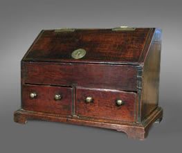 Welsh oak miniature bureau, the sloping front enclosing a fitted interior and well