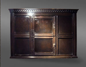 wall-hanging cupboard of unusual design and decorated with punchwork and pierced geometric designs, the cornice has broken dentil embellishment above a pair of central doors flanked by panels, circa 1700